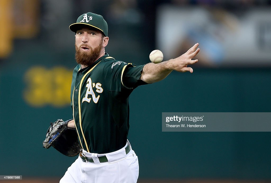 Ike Davis of the Oakland Athletics throws the ball away for an error attempting to get it to pitcher Jesse Hahn covering first base against the...