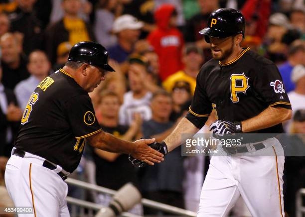Ike Davis of the Pittsburgh Pirates celebrates with third base coach Nick Leyva after hitting a solo home run in the sixth inning against the Detroit...