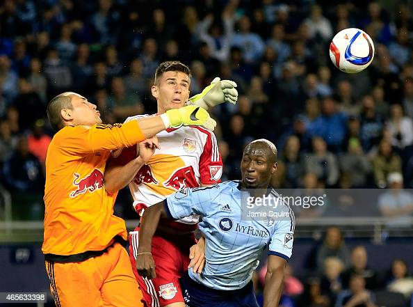 Ike Opara of Sporting KC and Damien Perrinelle of New York Red Bulls compete for a head ball as goalkeeper Luis Robles breaks it up during the game...