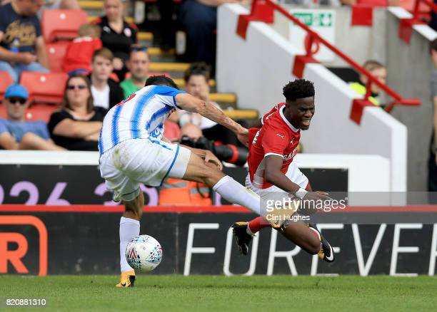Ike Ugbo of Barnsley is tackled by Christopher Schindler of Huddersfield Town during the pre season friendly at Oakwell Stadium on July 22 2017 in...