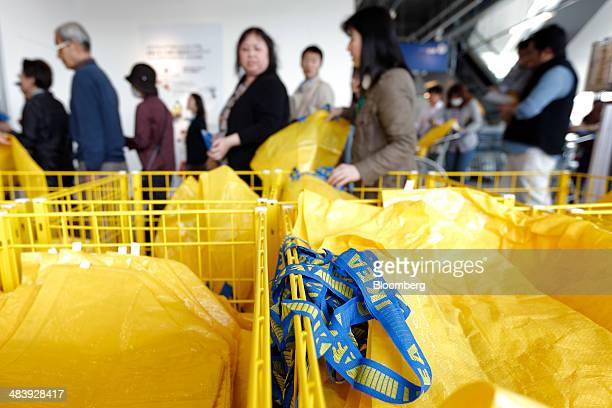 Ikea shopping bags sit in baskets as customers pick up the bags to shop during the opening of an Ikea store in Tokyo Japan on Thursday April 10 2014...