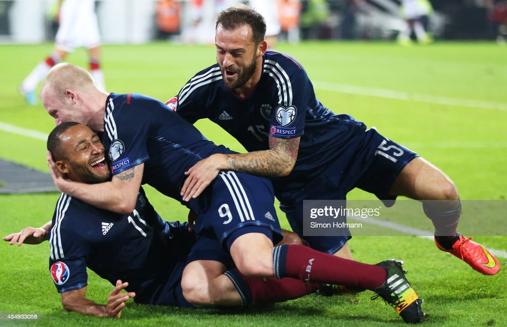 Ikechi Anya of Scotland celebrates his team's first goal with his team mates Steven Naismith (C) and Steven Fletcher (R) during the EURO 2016 Qualifier match between Germany and Scotland at Signal Iduna Park on September 7, 2014 in Dortmund, Germany.
