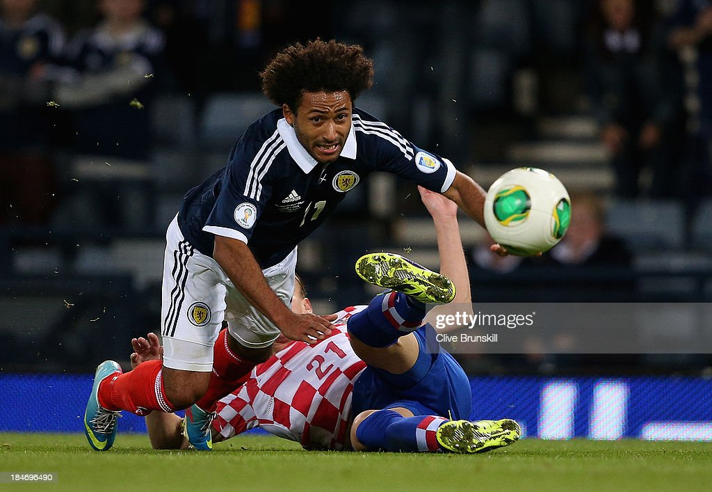 Ikechi Anya of Scotland is tackled by Domagoj Vida of Croatia during the FIFA 2014 World Cup Qualifying Group A match between Scotland and Croatia at Hampden Park on October 15, 2013 in Glasgow, Scotland.