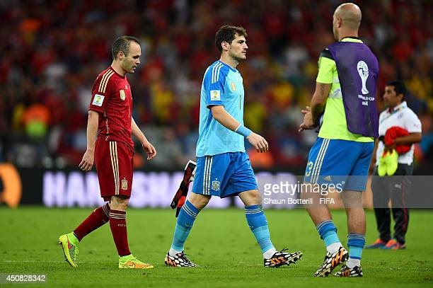 Iker Casillas and Andres Iniesta of Spain walk off the pitch after the 2014 FIFA World Cup Brazil Group B match between Spain and Chile at Estadio...