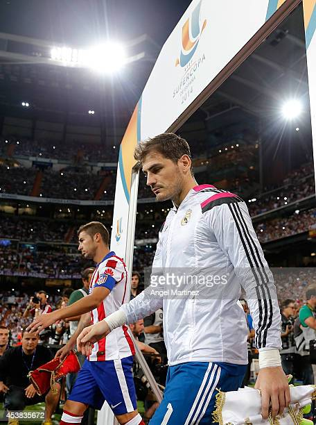 Iker Casillas of Real Madrid and Gabi Fernandez of Atletico de Madrid walk onto the field before the Supercopa first leg match between Real Madrid...