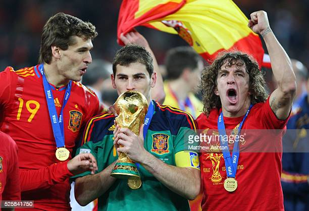 Iker Casillas of Spain kisses the FIFA World Cup Trophy as he celebrates Spain becoming the 2010 FIFA World Cup Champions with Fernando Llorente and...