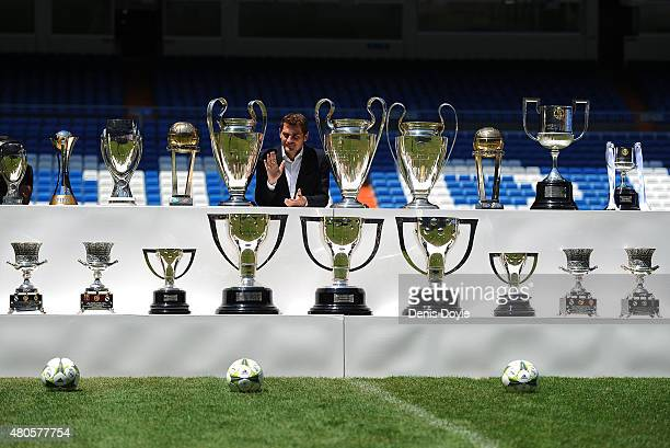 Iker Casillas poses behind trophies he has won during his career in Real Madrid after holding a press conference with Real president Florentino Perez...