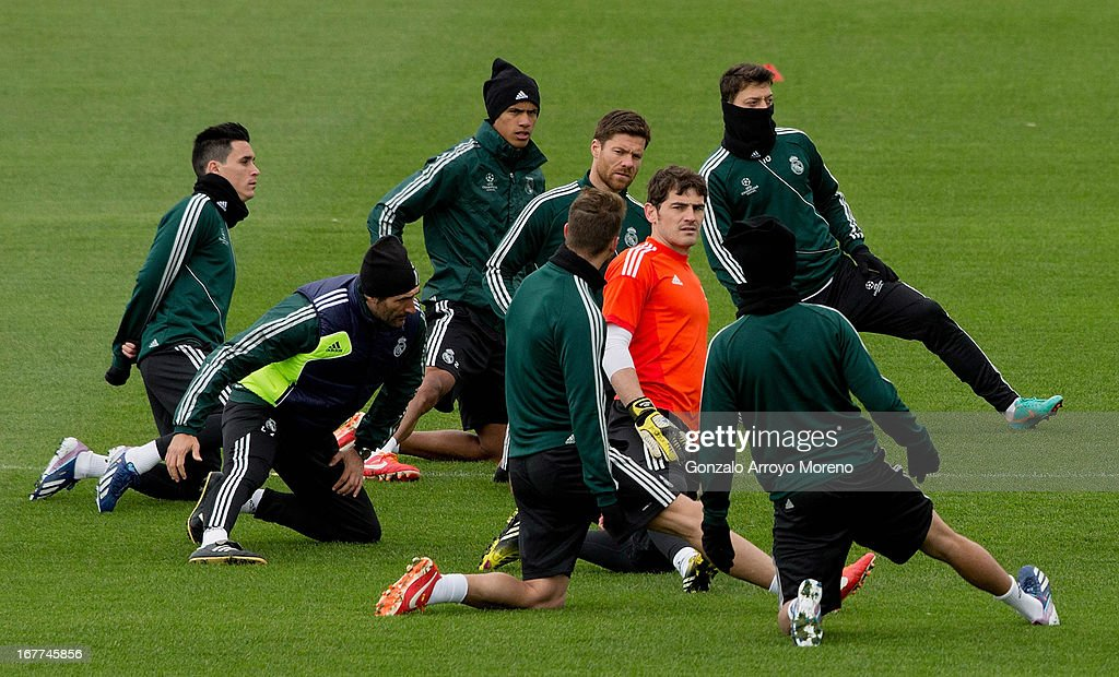 Iker Casillas (3rd R) warms up with team-mates <a gi-track='captionPersonalityLinkClicked' href=/galleries/search?phrase=Sergio+Ramos+-+Jugador+de+f%C3%BAtbol&family=editorial&specificpeople=491009 ng-click='$event.stopPropagation()'>Sergio Ramos</a> (5th R), <a gi-track='captionPersonalityLinkClicked' href=/galleries/search?phrase=Xabi+Alonso&family=editorial&specificpeople=213833 ng-click='$event.stopPropagation()'>Xabi Alonso</a> (3rd L), Raphael Varane (4th L), Jose Maria Callejon (L) and Mesut Ozil (2nd R) during a training session ahead of the UEFA Champions League Semifinal second leg match between Real Madrid and Borussia Dortmund at the Valdebebas training ground on April 29, 2013 in Madrid, Spain.
