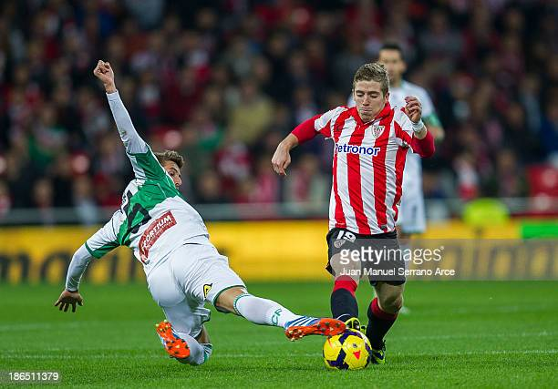 Iker Muniain of Athletic Club Bilbao competes for the ball with Ruben Perez of Elche FC during the La Liga match between Athletic Club Bilbao and...
