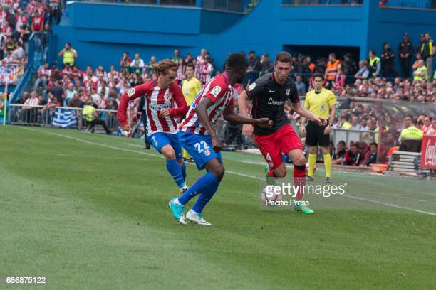 Iker Muniain try to evade Thomas Partey and Antoine Griezmann pressure Muniain during the football match between Atletico de Madrid and Athletic de...