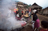Iko villagers gather around a rice thresher in the village of Ban Long Muay a twoday walk from Muang Sing in Northern Laos The Iko people can be...
