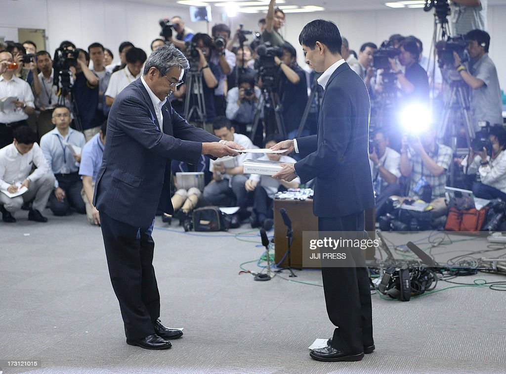 Ikuo Morinaka (L), exective of Kansai Electric Power Co., hands an application to Tomoya Ichimura (R), official of Japan's Nuclear Regulation Authority (NRA) in Tokyo on July 8, 2013. Japanese utilities on July 8 asked regulators for permission to turn on 10 nuclear reactors, a move that could presage a widespread restart of atomic power more than two years after the Fukushima disaster. JAPAN