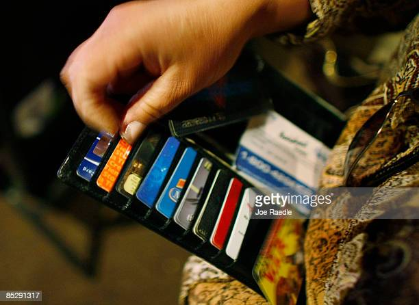 Ileana Garcia looks in her wallet for credit cards she wants to melt over a hot plate as she tries to dig herself out of credit card debt during a...