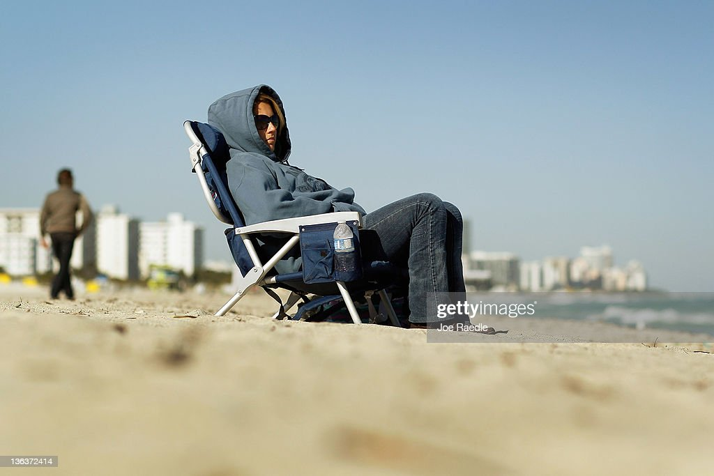 Ilene Ackerman bundles up against the cool weather as she watches her boyfriend surf on January 3, 2012 in Miami Beach, Florida. South Florida experienced one of the coolest days of the winter season and tomorrow is expected to be colder with temperatures expected to dip into the 30s inland and low 40s on the coast.