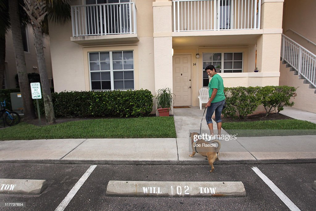 Ilene Rodriguez returns home after taking Rusty out for a walk in The Village of Abacoa condominium complex where the condo association will begin testing dog feces to match its DNA to the dogs whose owners who are not picking up after their pets on June 30, 2011 in Jupiter, Florida. Beginning August 1, 2011 dog owners who live in the condos must pay a $200 one-time fee for a DNA swab to be taken from their dog's mouth to be held on file. If a dog's feces are found, a sample is sent to the DNA Pet World Registry to determine the dog's DNA and they match that with the one on file to determine who the owner is and than a fine will be issued for not picking up after their pet.