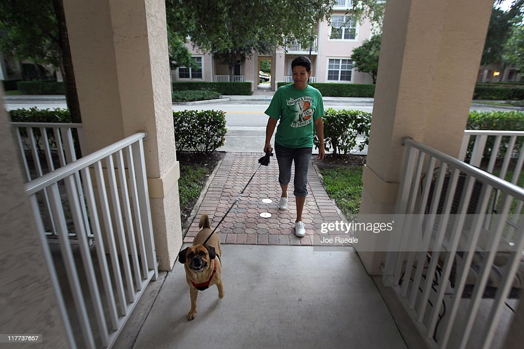 Ilene Rodriguez takes Rusty out for a walk in The Village of Abacoa condominium complex where the condo association will begin testing dog feces to match its DNA to the dogs whose owners who are not picking up after their pets on June 30, 2011 in Jupiter, Florida. Beginning August 1, 2011 dog owners who live in the condos must pay a $200 one-time fee for a DNA swab to be taken from their dog's mouth to be held on file. If a dog's feces are found, a sample is sent to the DNA Pet World Registry to determine the dog's DNA and they match that with the one on file to determine who the owner is and than a fine will be issued for not picking up after their pet.