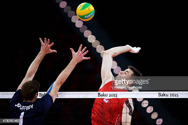 Ilia Vlasov of Russia and Quentin Jouffroy of France jump at the net during the Men's Volleyball quarter final match between France and Russia during...