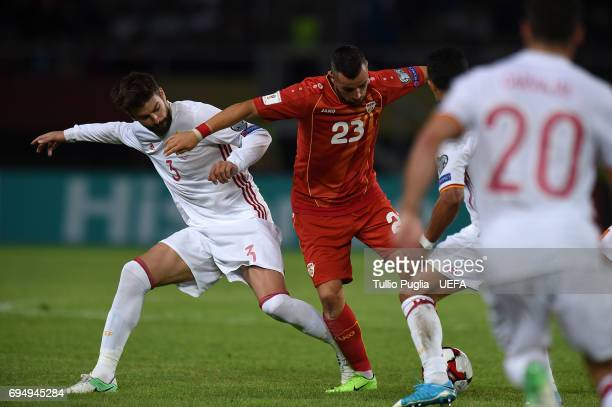 Ilija Nestorovski of FYR Macedonia is challenged by Gerard Pique of Spain during the FIFA 2018 World Cup Qualifier between FYR Macedonia and Spain at...