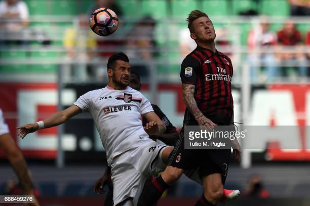 Ilija Nestorovski of Palermo and Juraj Kucka of Milan jump for a header during the Serie A match between AC Milan and US Citta di Palermo at Stadio...
