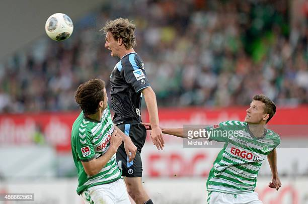 Ilir Azemi and Tom Weilandt of Fuerth compete with Kai Buelow of Muenchen for the ball during the Second Bundesliga match between Greuther Fuerth and...