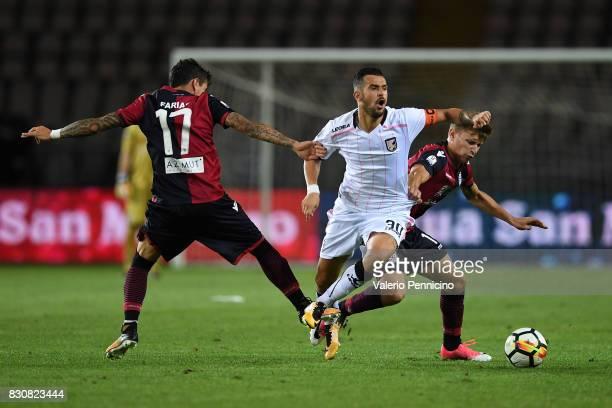 Ilja Nestorovski of US Citta di Palermo is challenged by Diego Farias and Nicolo Barella of Cagliari Calcio during the TIM Cup match between Cagliari...