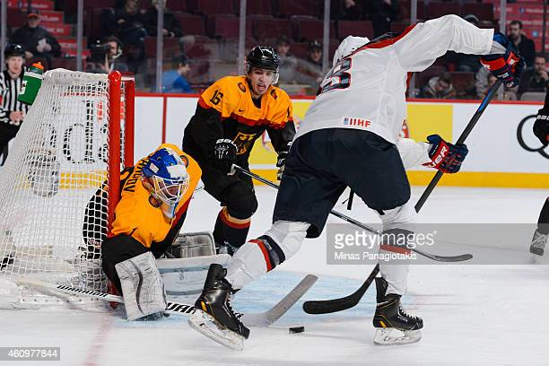 Ilja Sharipov of Team Germany pokes the puck from Sonny Milano of Team United States during the 2015 IIHF World Junior Hockey Championship game at...