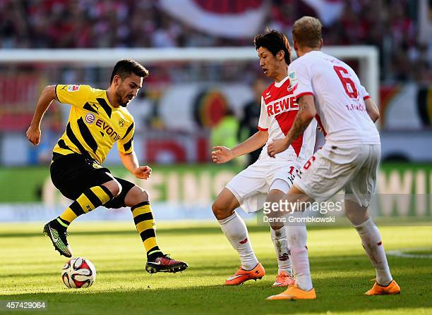 Ilkay Guendogan of Borussia Dortmund is challenged byYuya Osako of 1 FC Koeln during the Bundesliga match between 1 FC Koeln and Borussia Dortmund at...