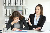 Ill businesswoman blowing and a colleague rejecting her at office