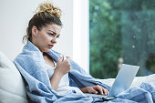Young ill woman in bed with laptop
