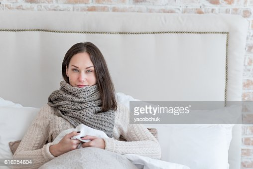 Ill young woman lying on the bed : Foto de stock