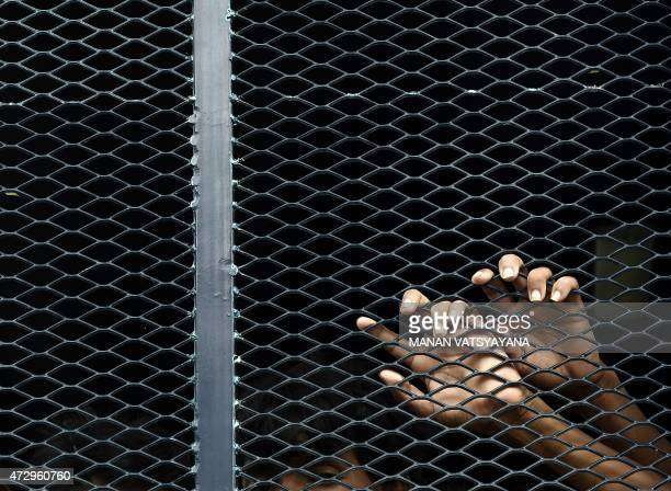 Illegal Bangladeshi migrants hold onto a metalmesh inside a police van at the Police headquarters in Langkawi on May 11 2015 after landing on...