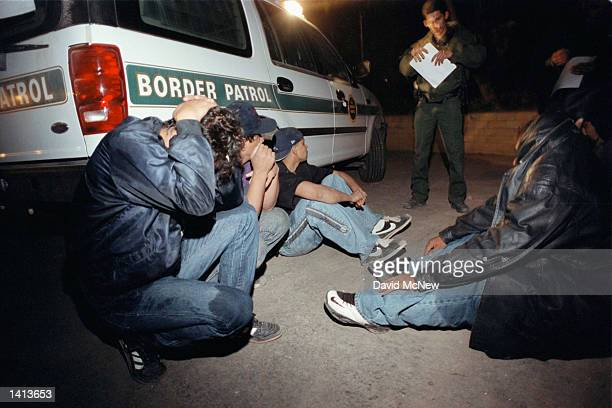 Illegal immigrants apprehended by United States Border Patrol hide their faces as they await transport for processing near Calexico Ca March 18 2000...