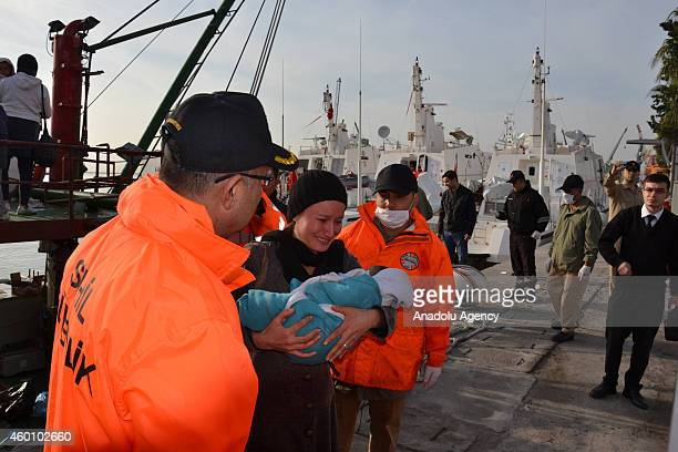 Illegal immigrants are escorted by the officers of Turkey's Coast Guard Mediterranean Region Command as they arrive in Mersin Turkey on December 06...