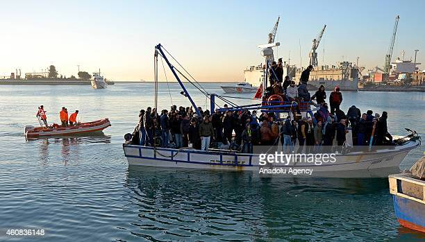 Illegal immigrants are escorted by the officers of Turkey's Coast Guard Mediterranean Region Command as they arrive in Mersin Turkey on December 26...