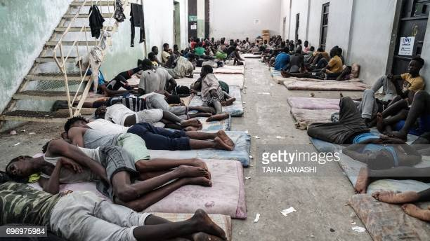 TOPSHOT Illegal immigrants are seen at a detention centre in Zawiyah 45 kilometres west of the Libyan capital Tripoli on June 17 2017 The Libyan...