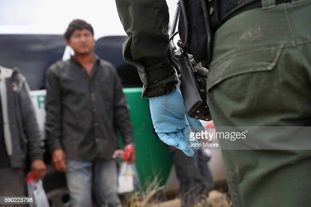 Illegal immigrants await transport to a detention center after being captured by US Border Patrol agents on August 16 2016 in Roma Texas Border...