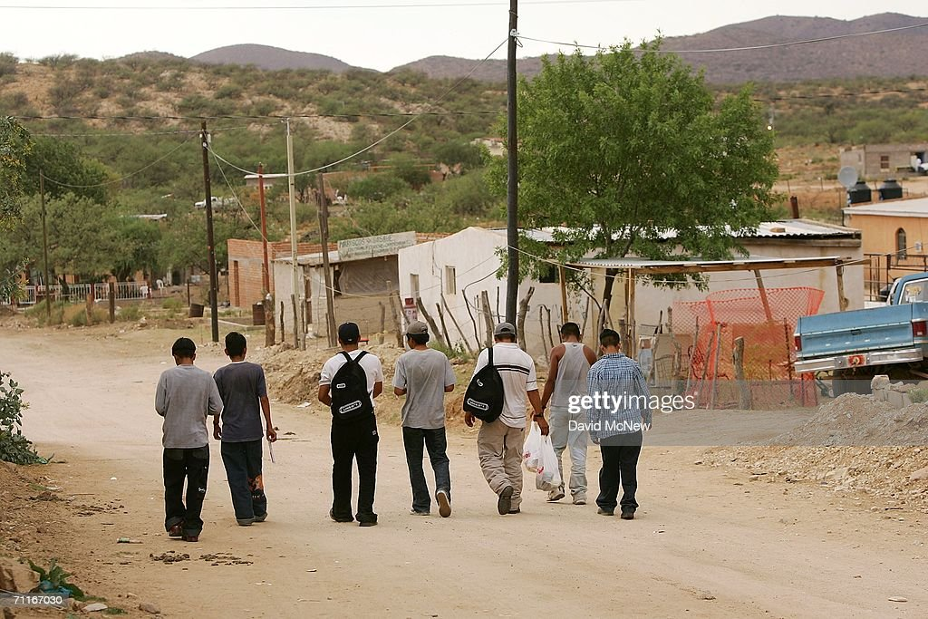 Illegal immigrants, having arrived from Altar, walk west toward a dangerous area where many robberies occur near the US-Mexico border on June 6, 2006 in the village of Sasabe, Mexico, 60 miles north of Altar. More illegal immigrants pass through Altar, where immigrant smuggling is the primary industry, than any other town. Available services include 'coyotes' or guides, transportation over 60 miles or more of dirt road in vans carrying as many as 25 people, about 150 'hospedajes' or guest houses, provisions, a free mobile clinic catering mostly to people who were hurt trying to cross the border, and groups who warn immigrants on the dangers of the trek and help those in need. From here, most immigrants are guided through Sasabe, where nightly robberies have become an industry and rape is common, then across the US-Mexico border to walk for about 45 miles through the desert before being picked up by smuggler vehicles. It is during the walk that most of the 473 deaths of 2005 occurred, mostly from exposure to extreme heat and fatigue.
