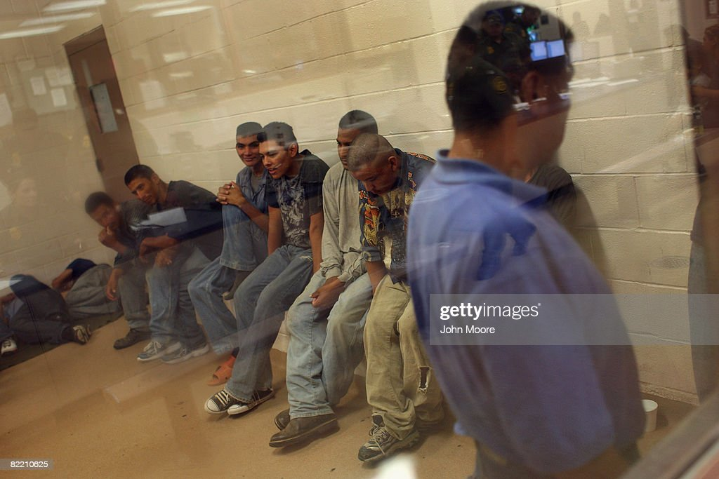 Illegal immigrants sit in a holding cell at a US Border Patrol station after they were caught crossing from Mexico into the United States August 7...