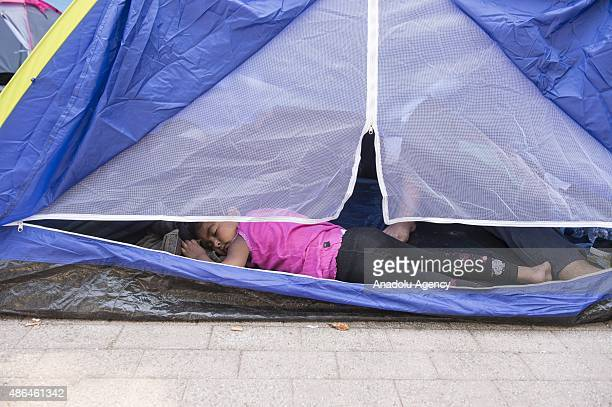 Illegal immigrants sleep in a tent at a street in Greece's Kos island on September 4 2015 Migrants who have illegally travelled from Mugla's Bodrum...