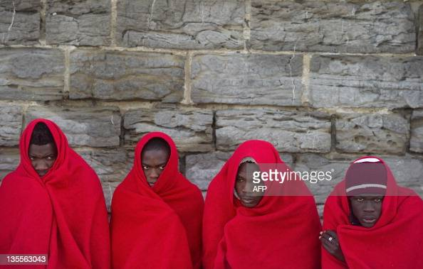 Illegal immigrants wait at Tarifa's port on December 12 2011 An inflatable vessel carrying 41 immigrants fourteen of them women and six chidren was...