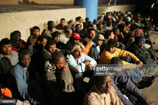 Illegal immigrants wait to be sent to a temporary holding centre for foreign nationals on June 13 2005 in Lampedusa Italy Lampedusa Island in the...