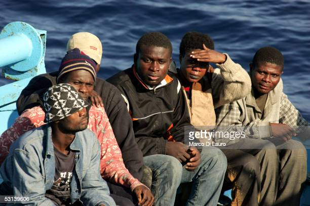 Illegal immigrants wait to be taken on board by a boat of Italian Custom Police 'Guardia di Finanza' on June 21 2005 in Lampedusa Italy Tens of...