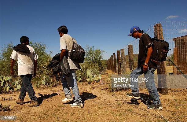 Illegal immigrants walk through an Indian ranch after being defeated by desert heat and the US Border Patrol July 31 2001 on the Tohono O''odham...