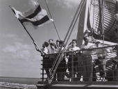 Illegal Jewish immigrants previously deported by the British to Mauritius wave what would become the Israeli flag as they arrive aboard the SS...