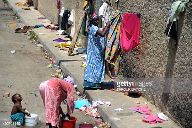 Illegal migrants from Niger hang clothes on a string on May 14 2014 after settling some of them for more than one year near the fruit market in the...