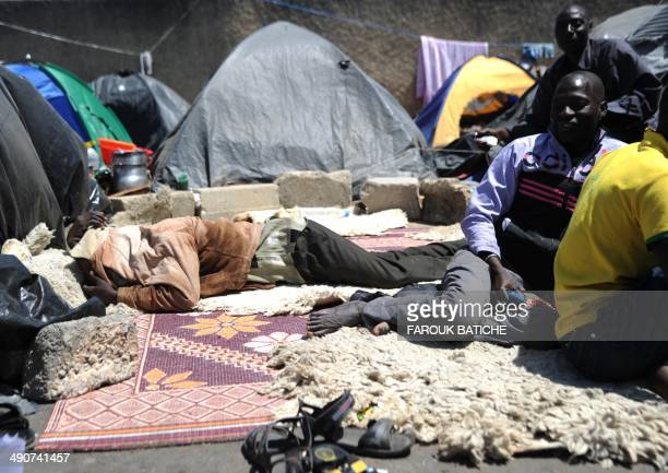 Illegal migrants from Niger sit next to their tents on May 14 2014 after settling some of them for more than one year near the fruit market in the...