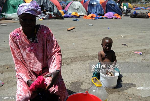 Illegal migrants from Niger wash clothes on May 14 2014 after settling some of them for more than one year near the fruit market in the Algerian town...