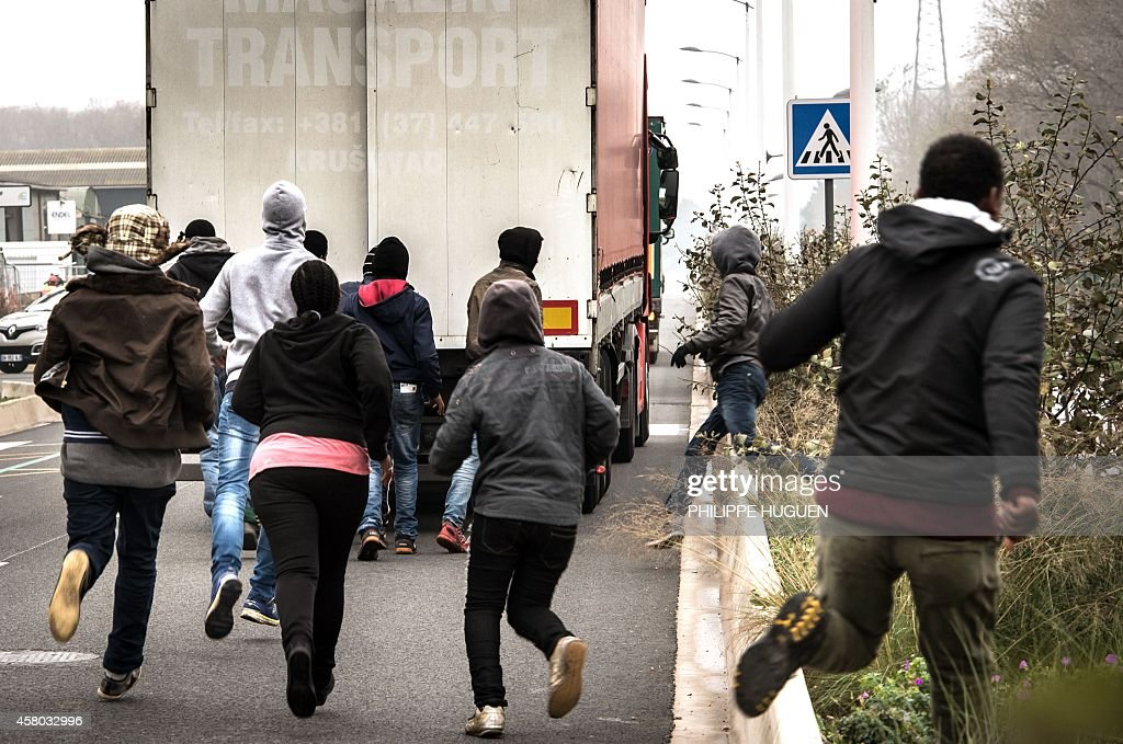 Illegal migrants run on October 29 2014 behing a truck to try to board it in the northeastern French port of Calais The mayor of Calais told...