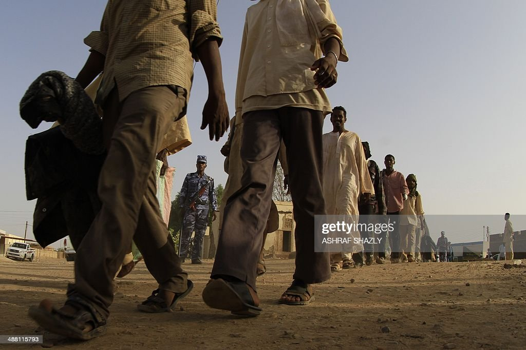 Illegal migrants who were abandoned in the desert by human traffickers gather at a military building in the northern Sudanese city of Dongola after a...