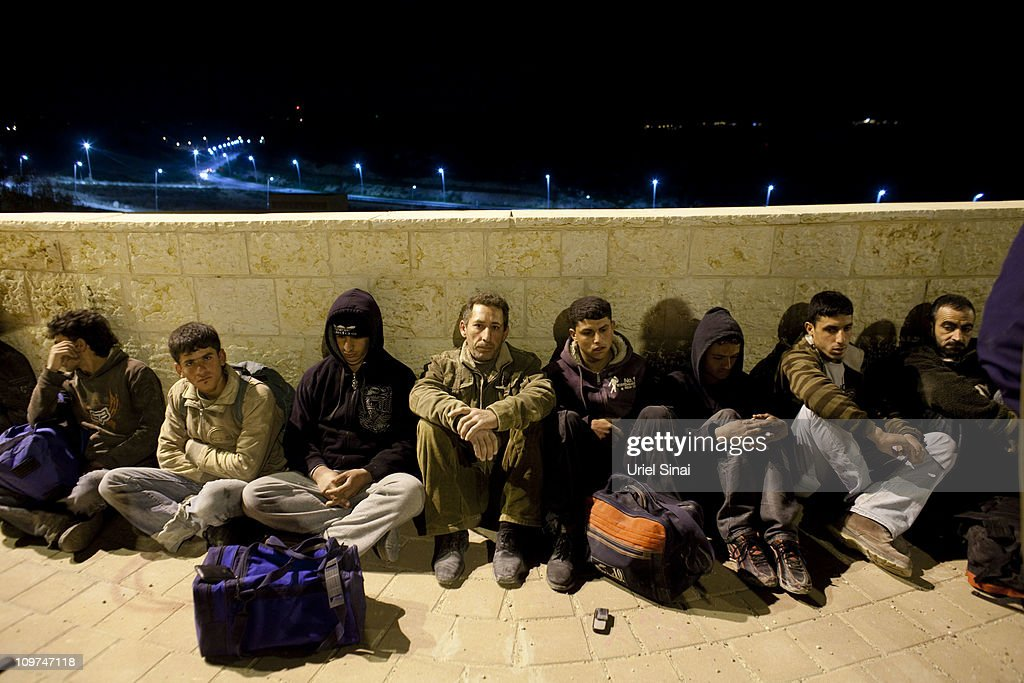 Illegal Palestinian workers from the West Bank sit on a sidewalk after they were caught on a construction site during a Lapid border police volunteer unit operation to seek out Palestinians who have crossed illegally into the town of Modiin, Israel on March 3, 2011. Some 7000 volunteers support Israel's regular Border police force on its routine activities to protect the country's boundaries.